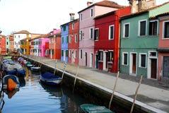 Kanal med fartyg och hem av många färger i Burano i Venedig i Italien Royaltyfria Bilder