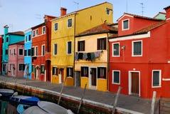 Kanal med fartyg och hem av många färger och kläder som ska torkas i Burano i Venedig i Italien Fotografering för Bildbyråer