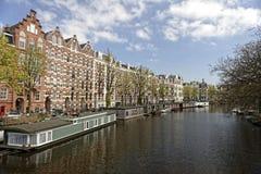 Kanal med husfartyg i Amsterdam royaltyfri foto
