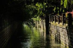 Kanal med stenbalustrader i träig stad av den soliga vårmornien royaltyfri bild