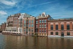 Kanal med tegelstenbyggnad, folk på restaurangen och solig blå himmel i Amsterdam royaltyfri fotografi