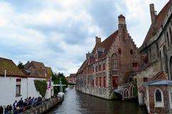 Kanal mellan de historiska byggnaderna i Brugge Arkivbild