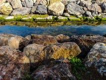 Kanal mit Felsen auf beiden Seiten und Reflexionen im Wasser stockbilder
