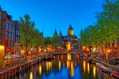Kanal och St Nicholas Church i Amsterdam på skymning, Nederländerna Berömd Amsterdam gränsmärke nära centralstation arkivbild