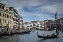 Kanal som är stor med den berömda Rialto bron och gondoler Arkivbilder