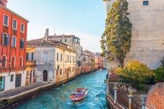 Kanal in Venedig mit einem kleinen Garten und einem Baum nahe dem Haus, auf dem Wasser ein kleines Motorboot stockbild