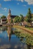 Kanal von Bäumen gesäumt mit Klappbrücke, Kirche, Backsteinhäusern in der Straße auf den Banken und sonnigem Tag bei Weesp Stockfotografie