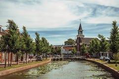 Kanal von Bäumen gesäumt mit Klappbrücke, Kirche und Backsteinhäusern in der Straße auf den Banken am sonnigen Tag in Weesp Stockfotografie