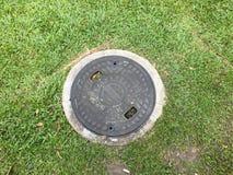 Kanaldeckel auf dem Gras Lizenzfreies Stockfoto