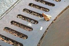 Kanaldeckelmetall, rustikaler quadratischer Abfluss in der Straße, Stahlgrill-Abwasserkanal oder Stockfotos