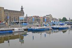 Kanalen kryssar omkring framme av den Amsterdam Centraal järnvägsstationen Royaltyfria Bilder