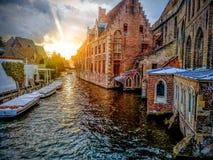 Kanaler av den medeltida staden av Brugge genom att använda de typiska fartygen över kanaler i Belgien royaltyfria bilder