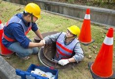 Kanalisationsarbeitskräfte im Einsteigeloch Stockfotografie