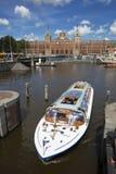 Kanalkreuzfahrtboot vor zentralem Bahnhof Amsterdams stockfoto