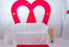Kanapa na scenie dla państwa młodzi, biały tła i czerwieni serca symbol Zdjęcie Royalty Free