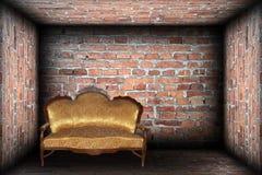 Kanapa w cegła skończonym pokoju Zdjęcie Royalty Free
