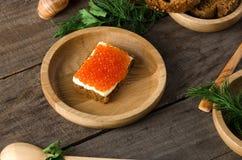 Kanapka łososiowego kawioru pucharu masła drewniany greenery Obrazy Stock