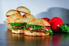 Kanapka - hamburger z hamburgerem, serem, pomidorem i cebulą na drewnianym tle, Obraz Royalty Free