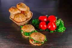 Kanapka - hamburger z hamburgerem, serem, pomidorem i cebulą na drewnianym tle, Obraz Stock