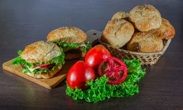 Kanapka - hamburger z hamburgerem, serem, pomidorem i cebulą na drewnianym tle, Zdjęcia Stock