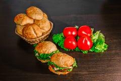 Kanapka - hamburger z hamburgerem, serem, pomidorem i cebulą na drewnianym tle, Fotografia Stock