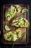 Kanapka - smorrebrod z brzdąc, avocado i kremowym serem na drewnianej desce, zdjęcia stock