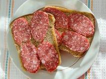 Kanapki czarny chleb z uwędzonymi kiełbasianymi kłamstwami na talerzu fotografia royalty free
