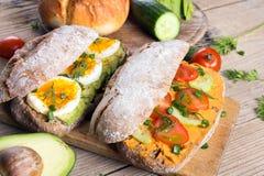 Kanapki z avocado, jajkami i pomidorem na drewnianym tle, Zdjęcie Stock