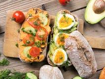 Kanapki z avocado, jajkami i pomidorem na drewnianym tle, Obraz Stock