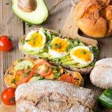 Kanapki z avocado, jajkami i pomidorem na drewnianym tle, Fotografia Stock