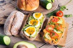 Kanapki z avocado, jajkami i pomidorem na drewnianym tle, Obrazy Royalty Free