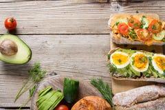 Kanapki z avocado, jajkami i pomidorem na drewnianym tle, Zdjęcie Royalty Free