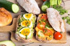 Kanapki z avocado, jajkami i pomidorem na drewnianym tle, Obraz Royalty Free