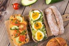 Kanapki z avocado, jajkami i pomidorem na drewnianym tle, Fotografia Royalty Free
