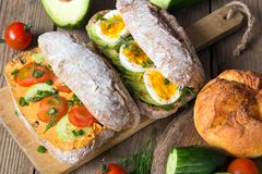 Kanapki z avocado, jajkami i pomidorem na drewnianym tle, Zdjęcia Stock