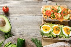 Kanapki z avocado, jajkami i pomidorem na drewnianym tle, Obrazy Stock