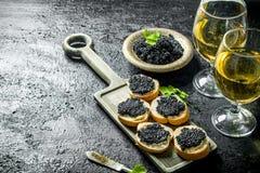 Kanapki z czarnym kawiorem i winem fotografia stock