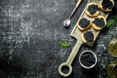 Kanapki z czarnym kawiorem, kawiorem w pucharze i bia?ym winem, fotografia stock