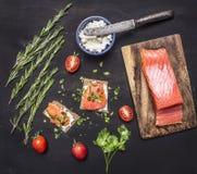 Kanapki z różowym łososiem przepasują up, curd ser, ziele i czereśniowi pomidory na drewnianym nieociosanym tło odgórnego widoku  Obrazy Stock