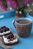 Kanapki z słodkim serem i jagodami, filiżanka kawy w błękitnym zdjęcie royalty free