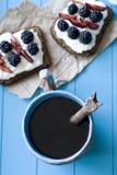 Kanapki z słodkim serem i jagodami, filiżanka kawy w błękitnym obrazy royalty free