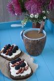 Kanapki z słodkim serem i jagodami, filiżanka kawy w błękitnym obraz royalty free