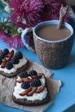 Kanapki z słodkim serem i jagodami, filiżanka kawy w błękitnym fotografia royalty free