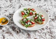 Kanapki z truskawkami, arugula i błękitnym serem na białym ceramicznym talerzu na lekkim tle, obraz stock
