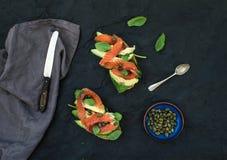 Kanapki z uwędzonym łososiem, avocado, szpinakiem, kaparem i basilem nad zmroku łupkiem, drylują tło Fotografia Royalty Free