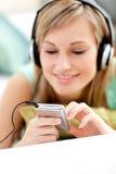 kanapy słuchająca łgarska muzyczna kobieta Obrazy Stock