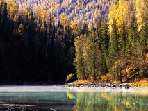 Kanas Lake in Autumn. `Kanas` is a Mongolian word meaning `lake in the canyon`. The main features of this Park are the `high mountain glacier lake` Kanas Lake Stock Photo