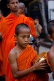 Kanchanaburi, Tailandia - 16 de marzo de 2014: El monje joven que espera recibe la comida de aldeanos Fotos de archivo libres de regalías