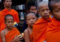 Kanchanaburi, Tailandia - 16 de marzo de 2014: Los monjes jovenes que esperan reciben la comida de aldeanos Imágenes de archivo libres de regalías