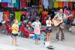 Kanchanaburi, Tailandia - 23 maggio 2014: I bambini non identificati cantano e chitarra adulta del gioco sulla via per ottenere i Immagini Stock